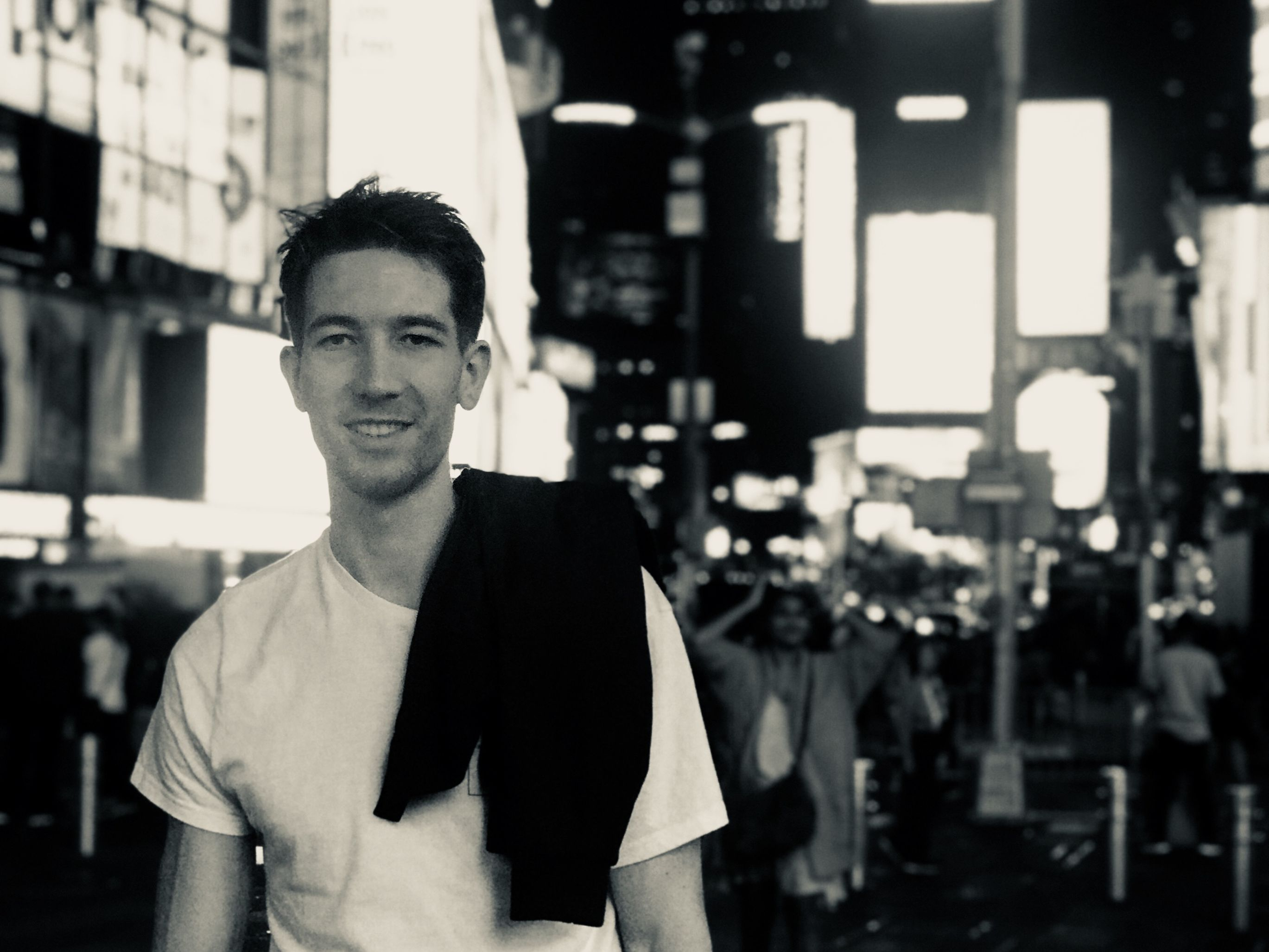 Black and white night time image of a man in a white tee-shirt