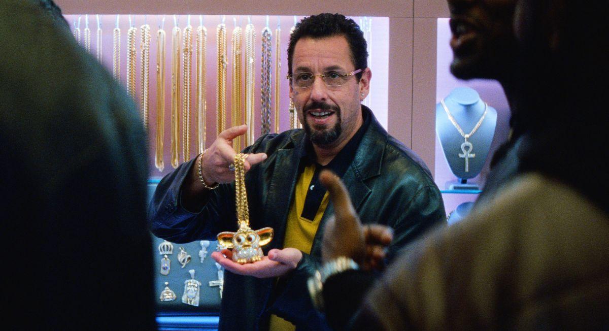 Actor Adam Sandler holding a jewel encrusted furby in the movie Uncut Gems