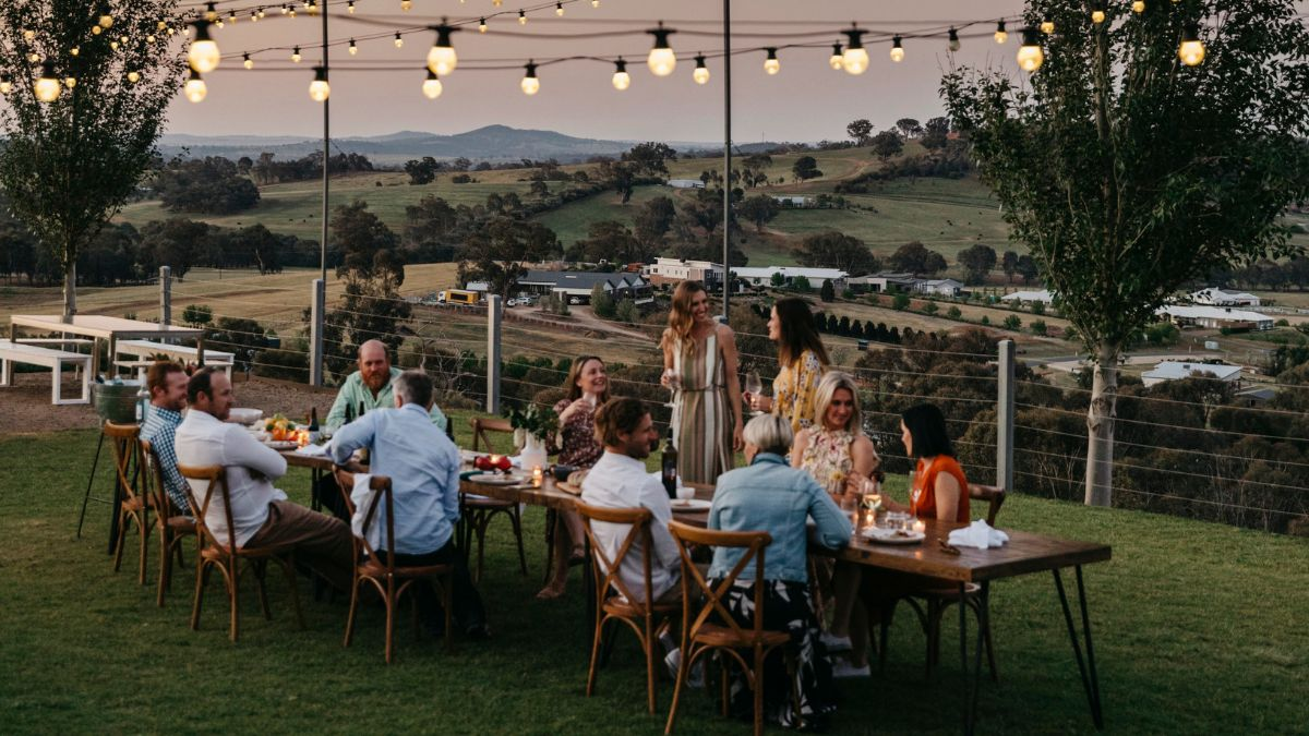 A group seated and standing around a long wooden table having a party. In the background are rolling hills