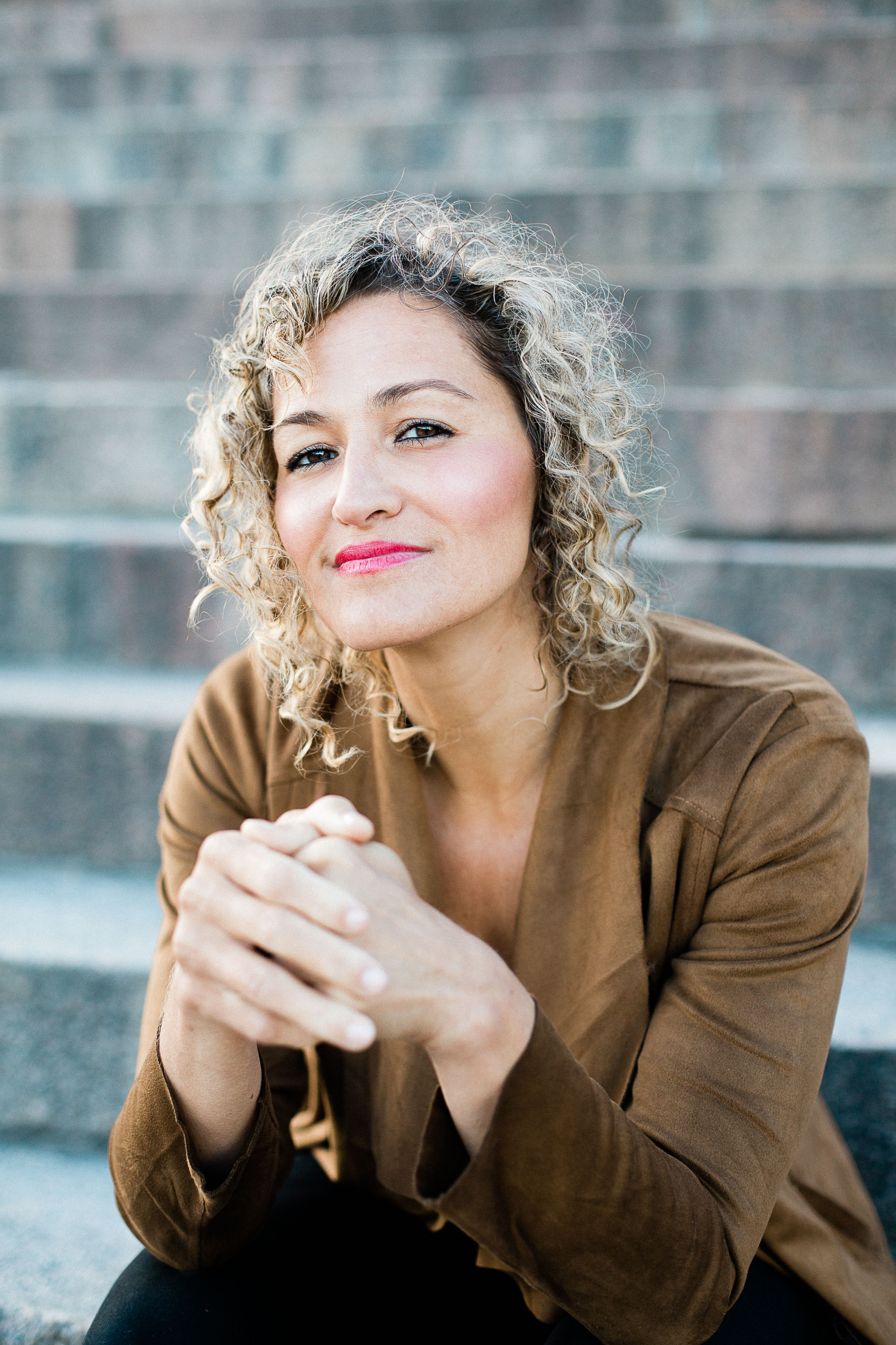 Dawn Jani Birley headshot - seatedwoman with blonde curly shoulder-length hair clasping hands loosely in front of herself, wearing a soft tan blazer and black pants
