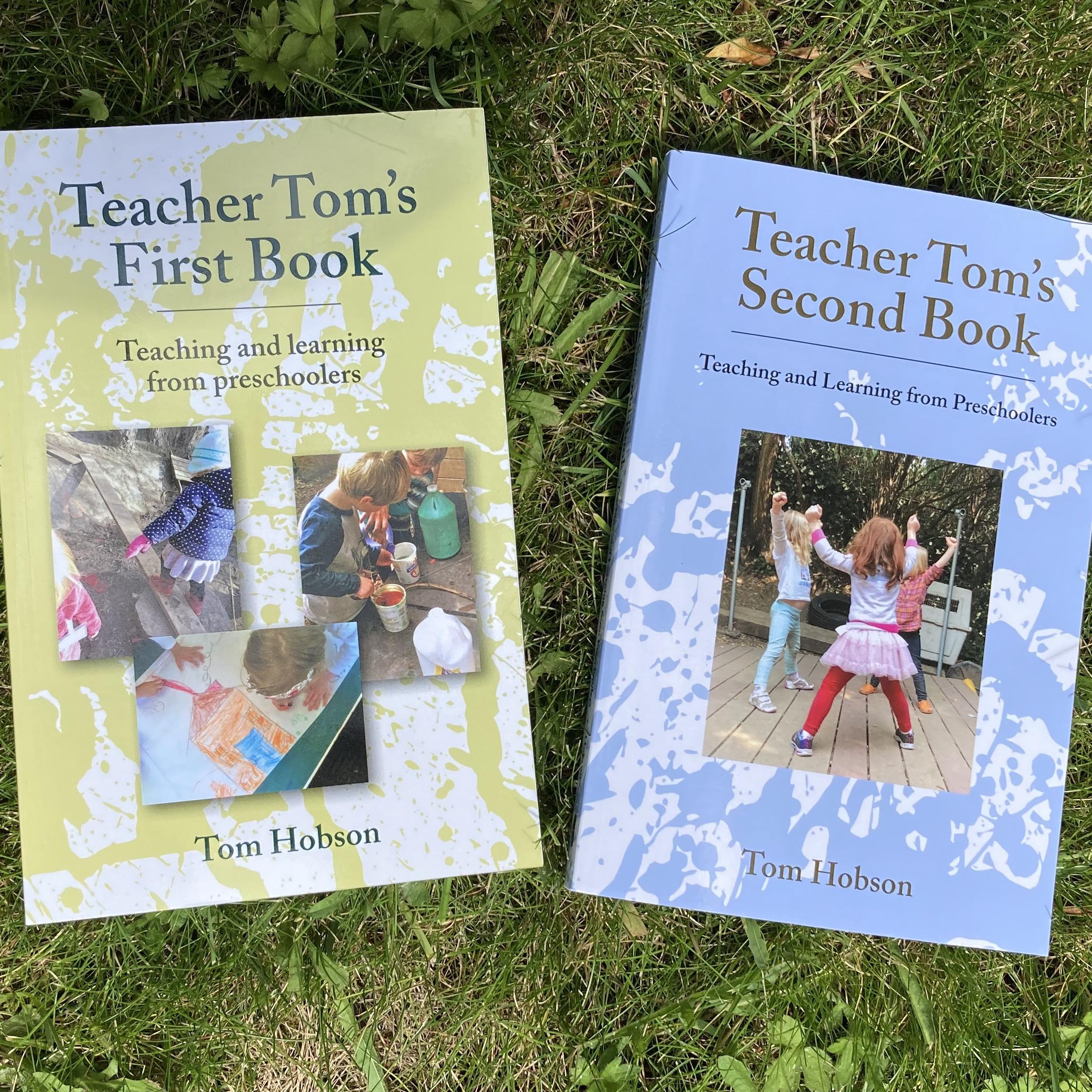 Teacher Tom's 2 books, lying on the grass
