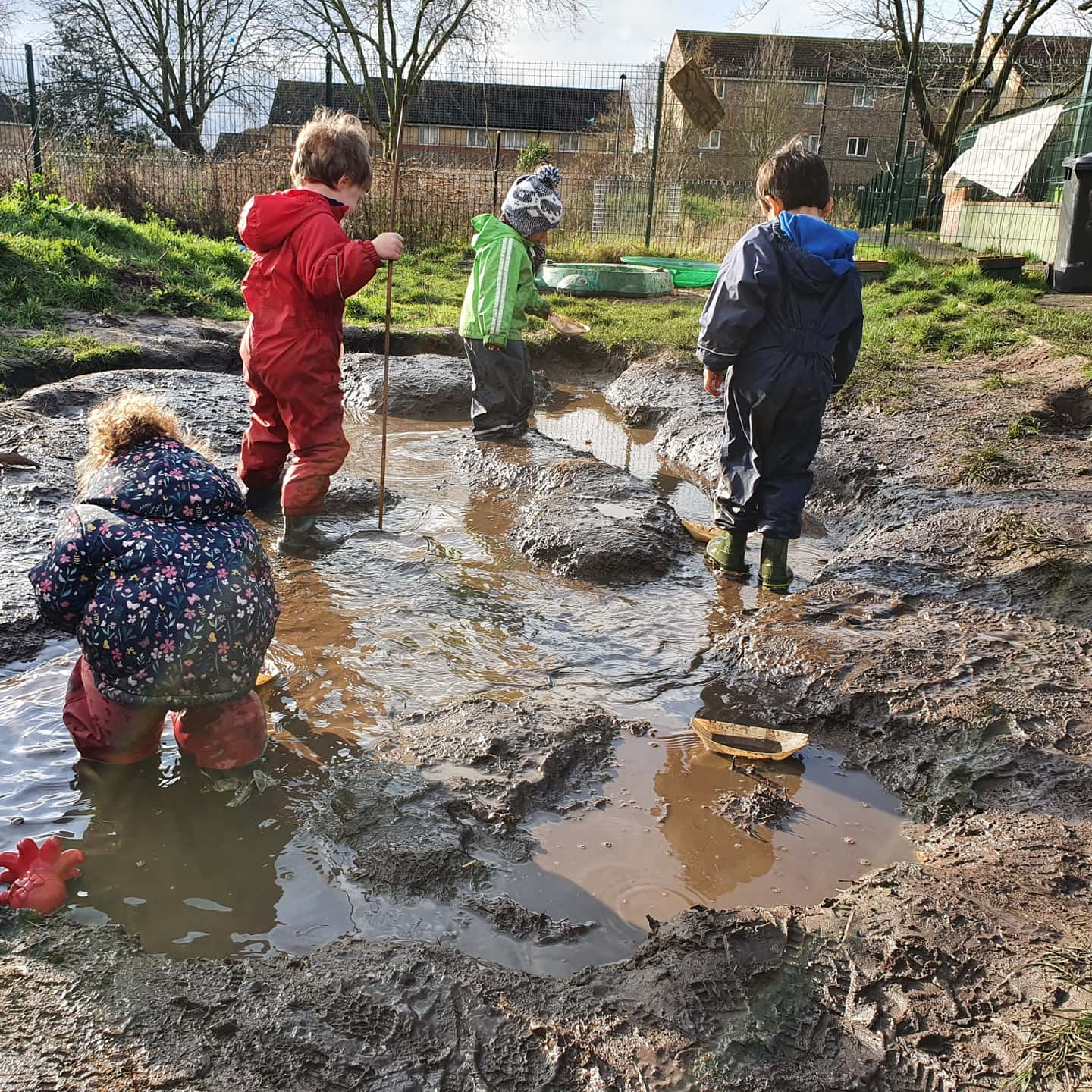 4 children in waterproof clothes playing in mud