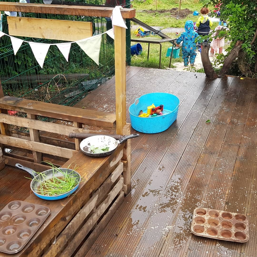 a counter made of wooden pallets with bowls of flowers and items for mud kitchen play