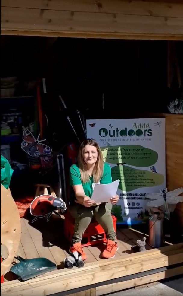 woman in a green tshirt sitting in a shed full of interesting items, reading a poem from a piece of paper