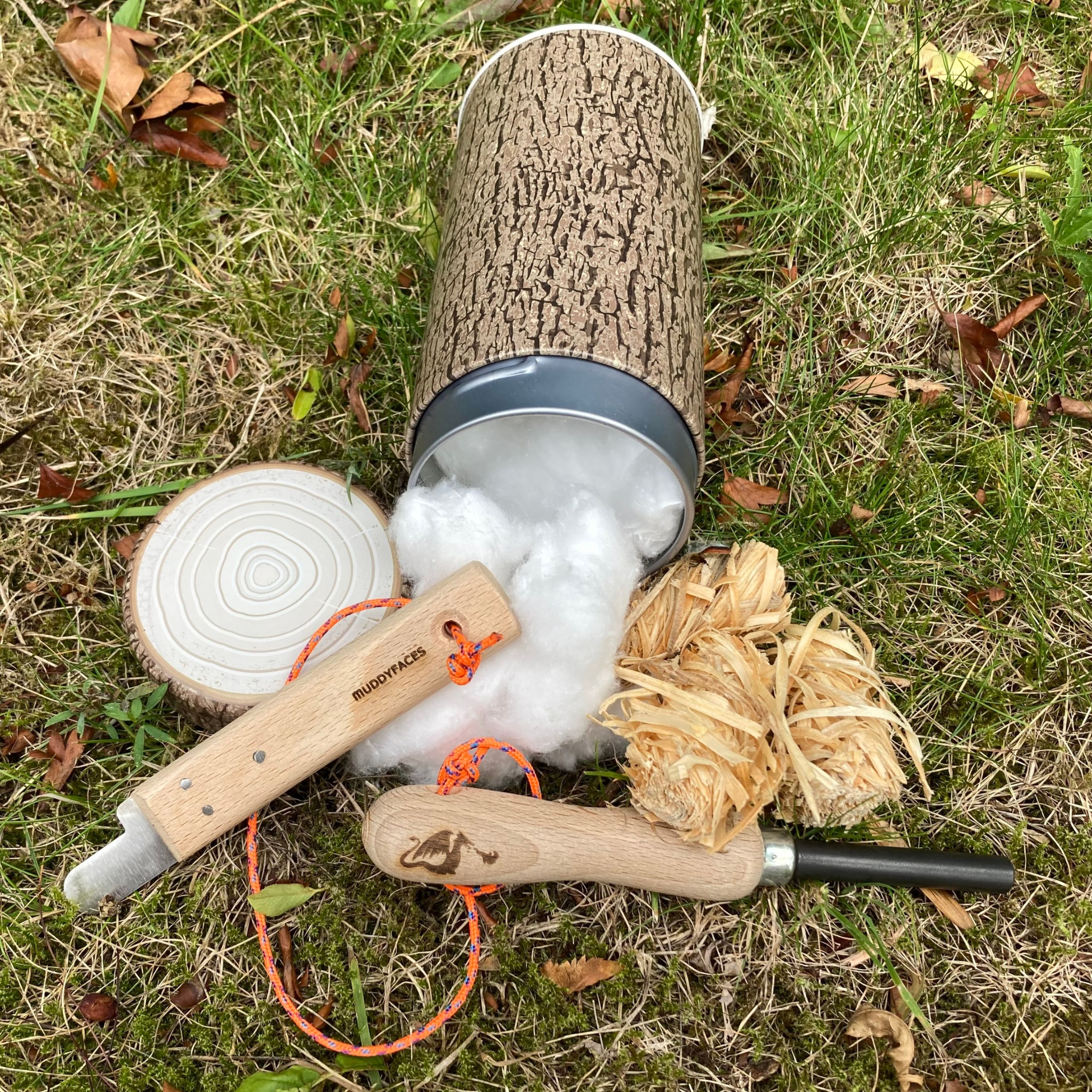 a log patterned tin full of cotton wool balls, with 3 wood strip ball firelighters and a dragons sneeze firelighter, lying on grass