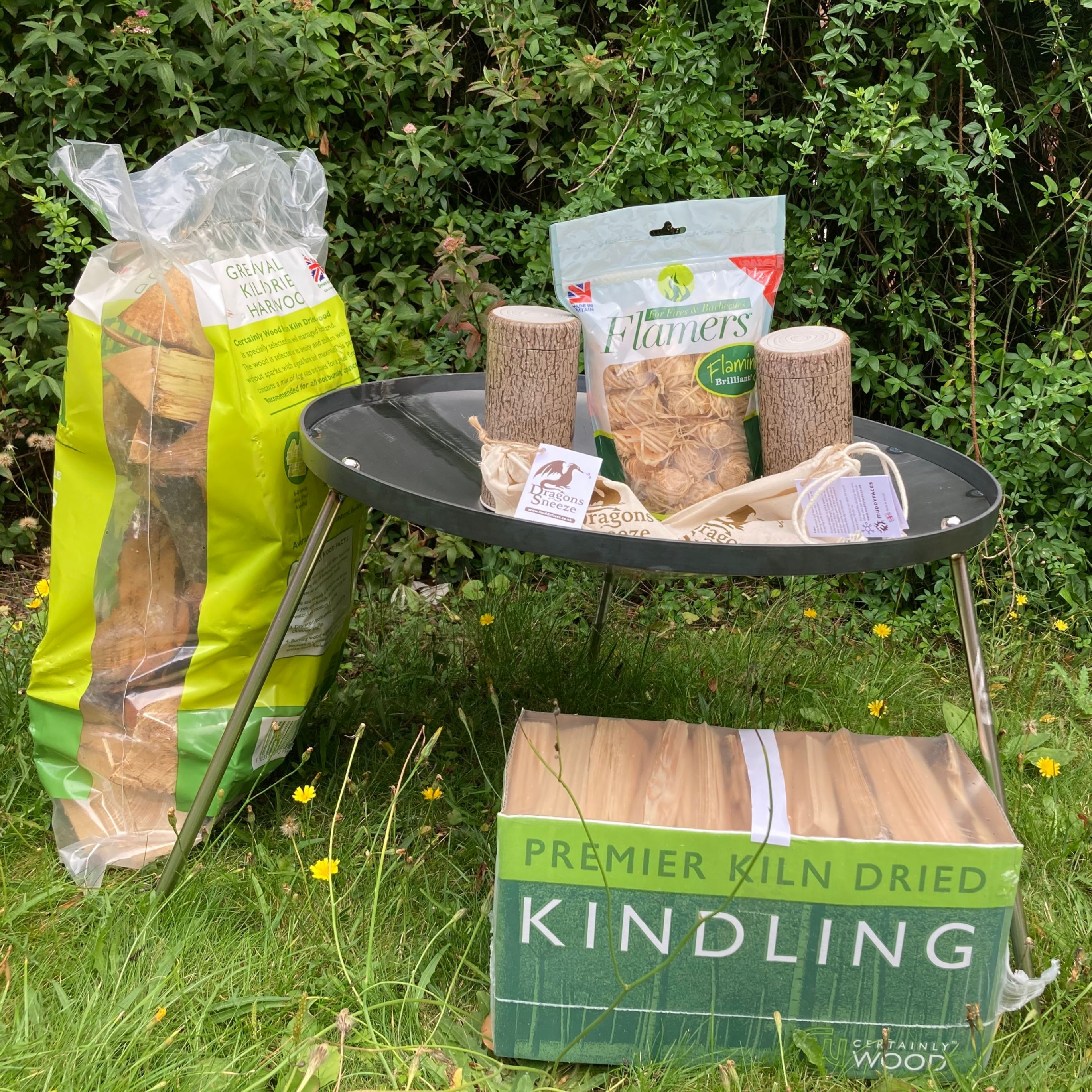bag and box of wooden kindling, metal fire pit, sitting inside 2 dragons sneeze fire steels, bag of natural fire starters and 2 log-shaped tins