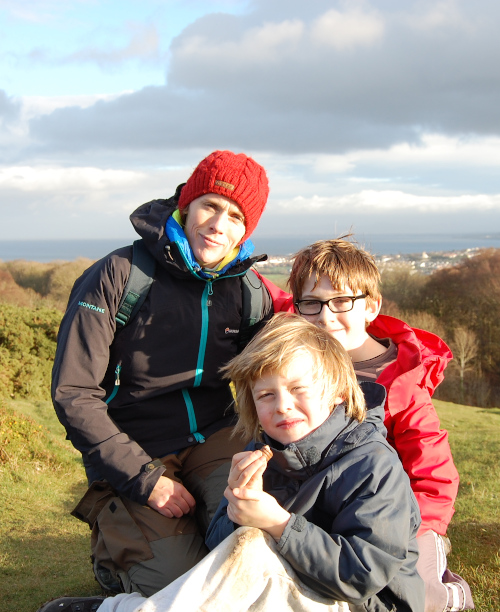 woman and 2 boys all in outdoor coats sitting at the top of a windy hill