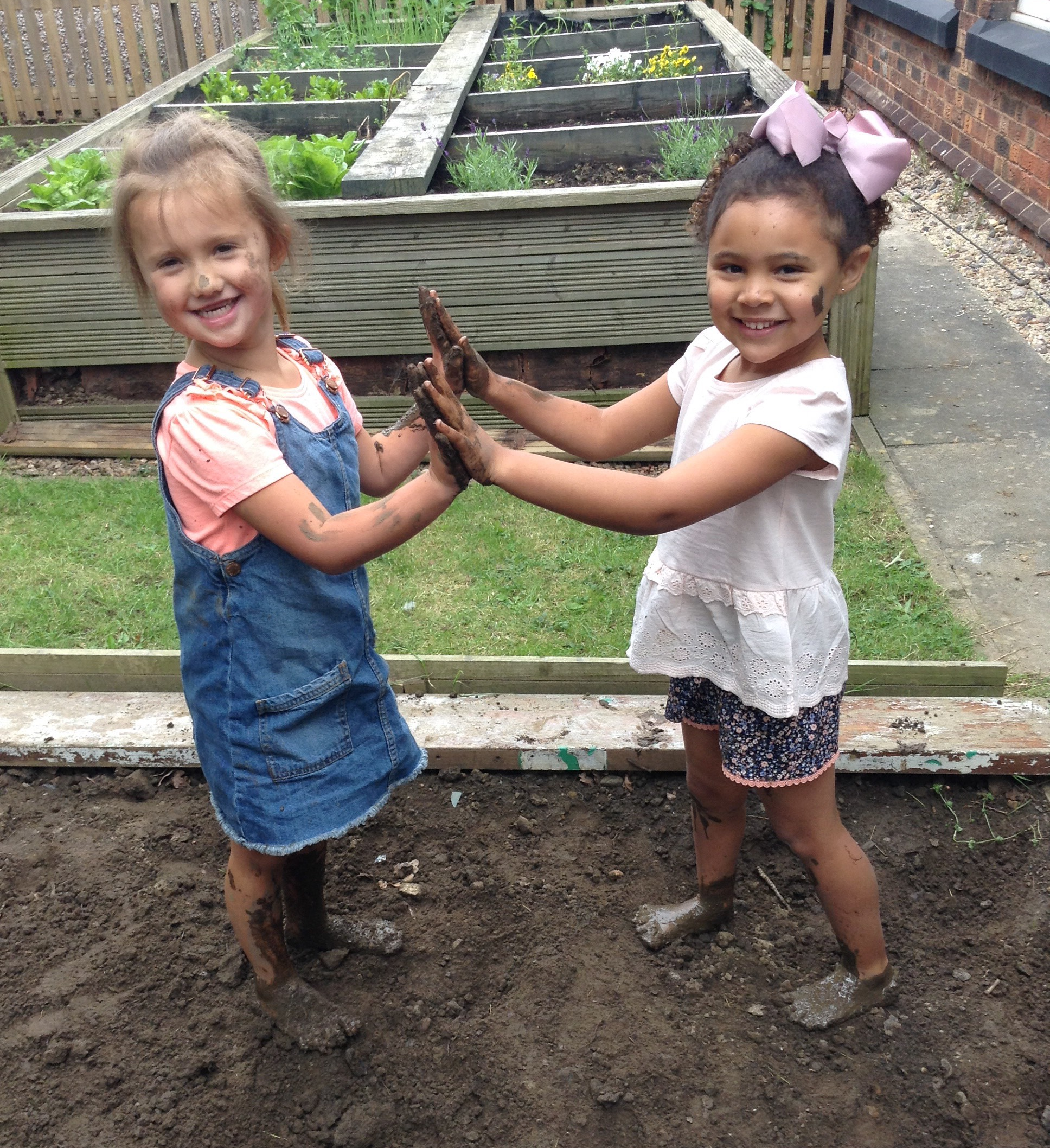 2 girls, one black one white, with muddy hands, feet and faces, standing facing each other clapping hands, and looking at the camera smiling