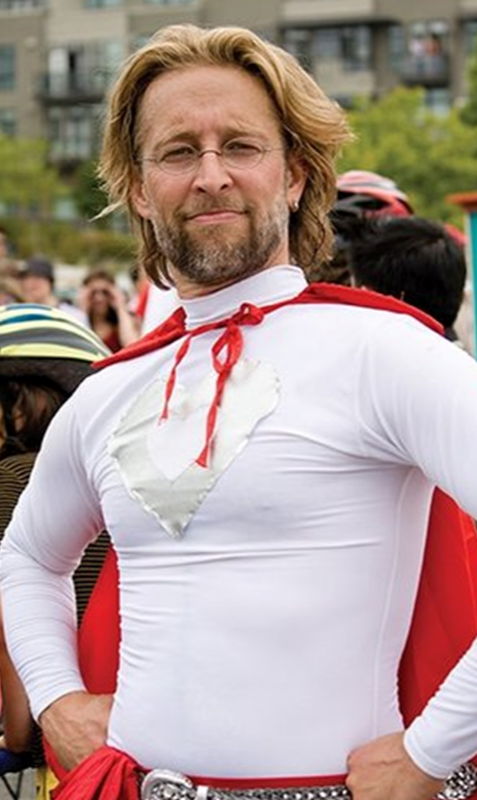 man in a white lycra top and red cape, with blond hair, glasses and beard, with hans on hips, smiling at the camera