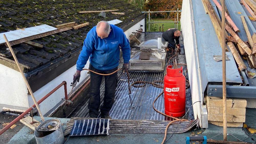 2 roofers repairing the roof on Haddenham Village Hall