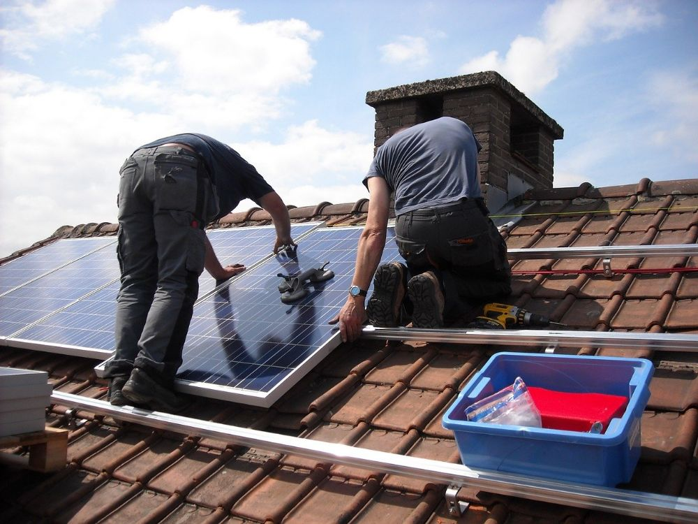 2 men installing solar panels to a roof