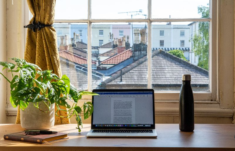 Photo of a desk space with an open laptop, a plant, and a re-usable water bottle in front of a big window with a view of the rooftops