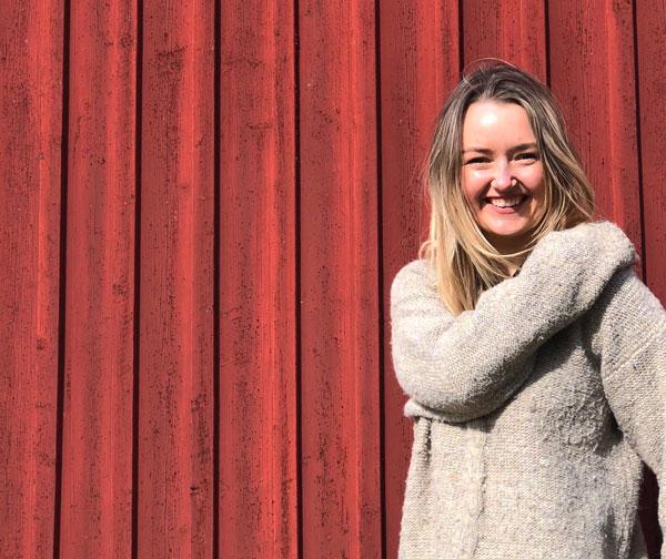 Foto, porträtt av Elin Persson framför en röd trävägg.