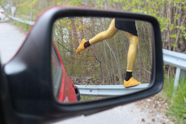 Foto av backspegel på bil. Däri speglas benen på en person ståendes på ett ben på ett vägräcke.