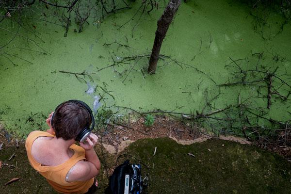 Foto, vy uppifrån. En person med hörlurar framför ett ljust grönt vattendrag.