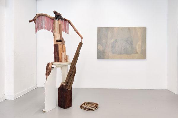 Foto, utställningsvy med skulptur/objekt i förgrunden och en målning på vit vägg i bakgrunden.