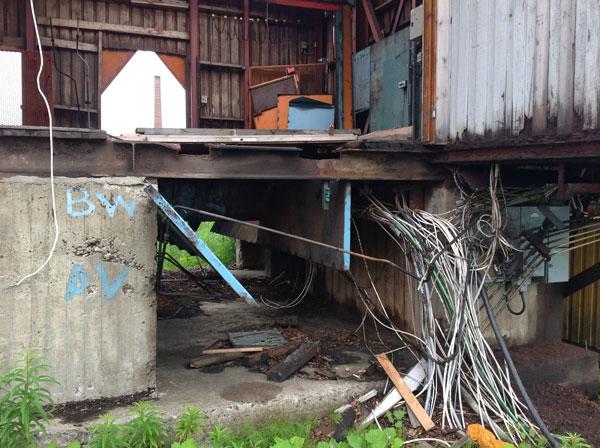 Foto: del av förfallen industri. Kablar, plåt och betong.