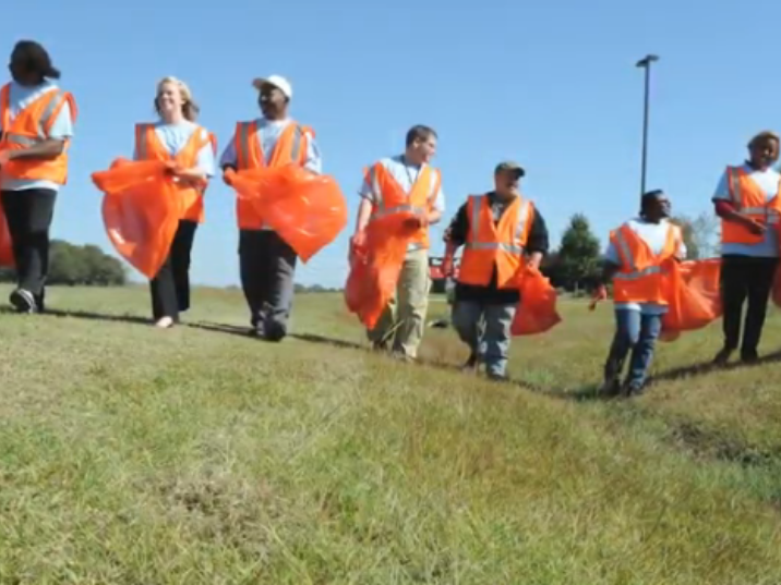 Volunteers picking up trash along roadway