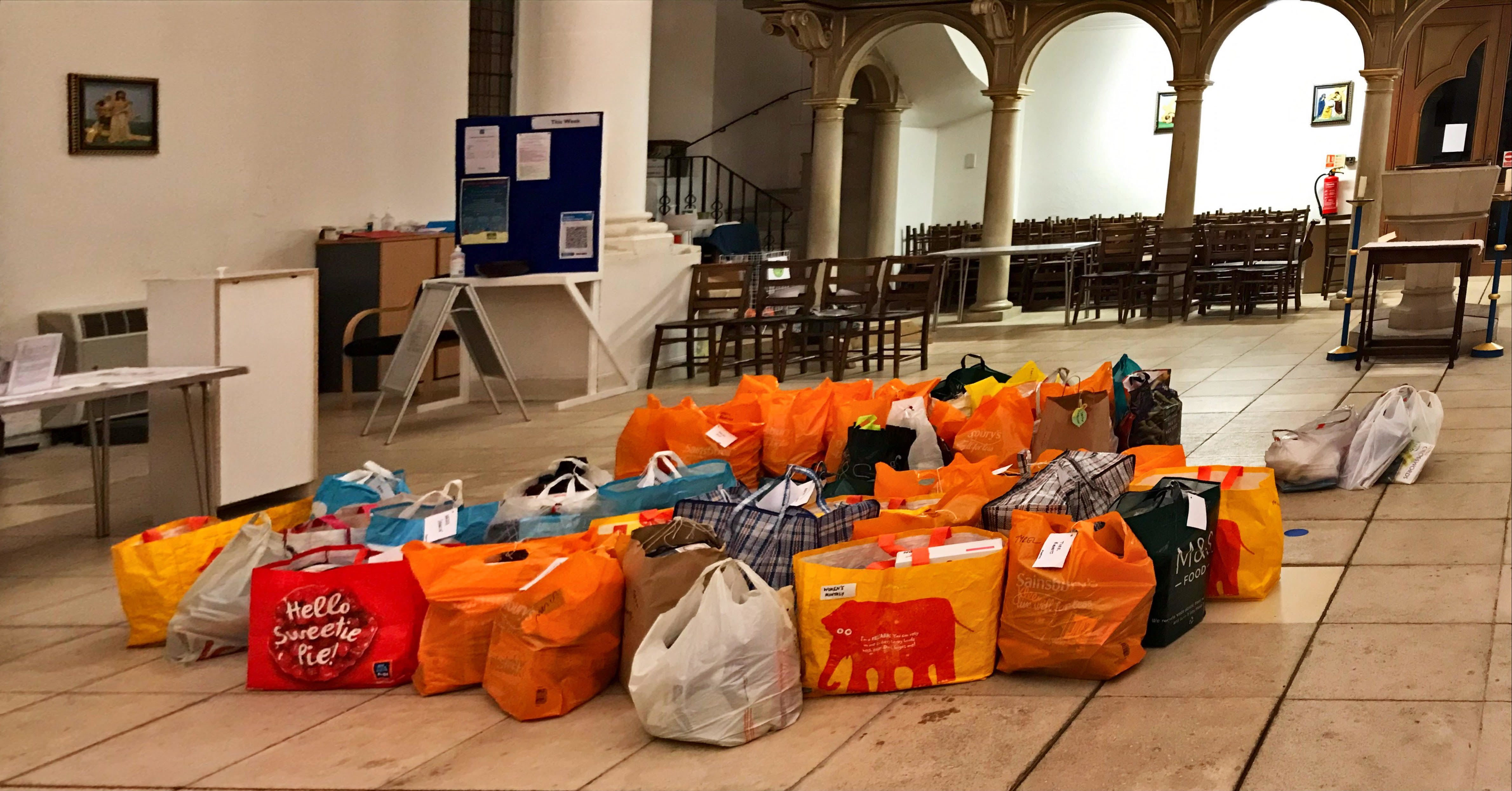 Lots of filled carrier bags piled near the back of church