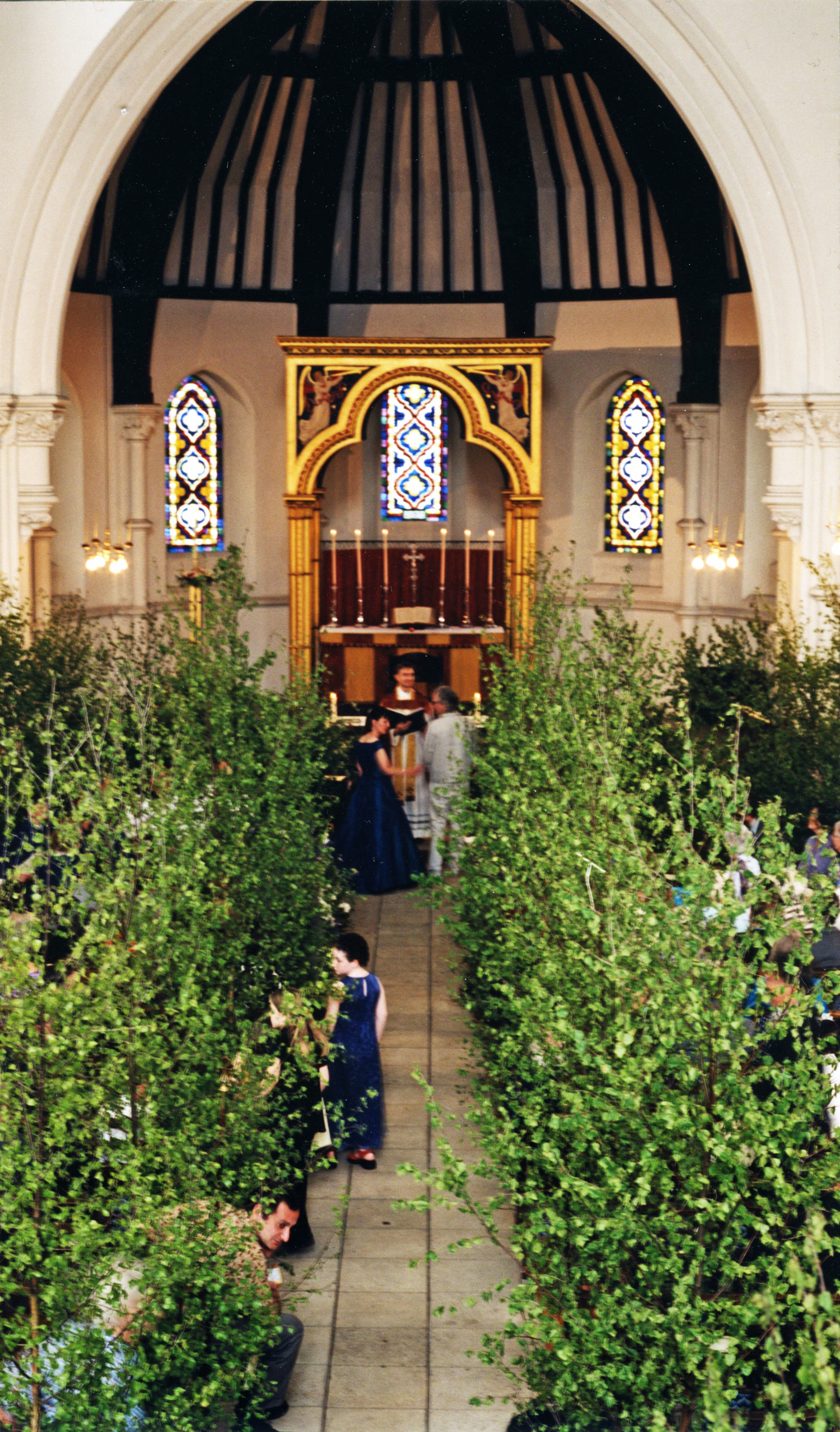 Wedding of Peter Bibby and Anne Clarke at St John's with small trees lining the aisle