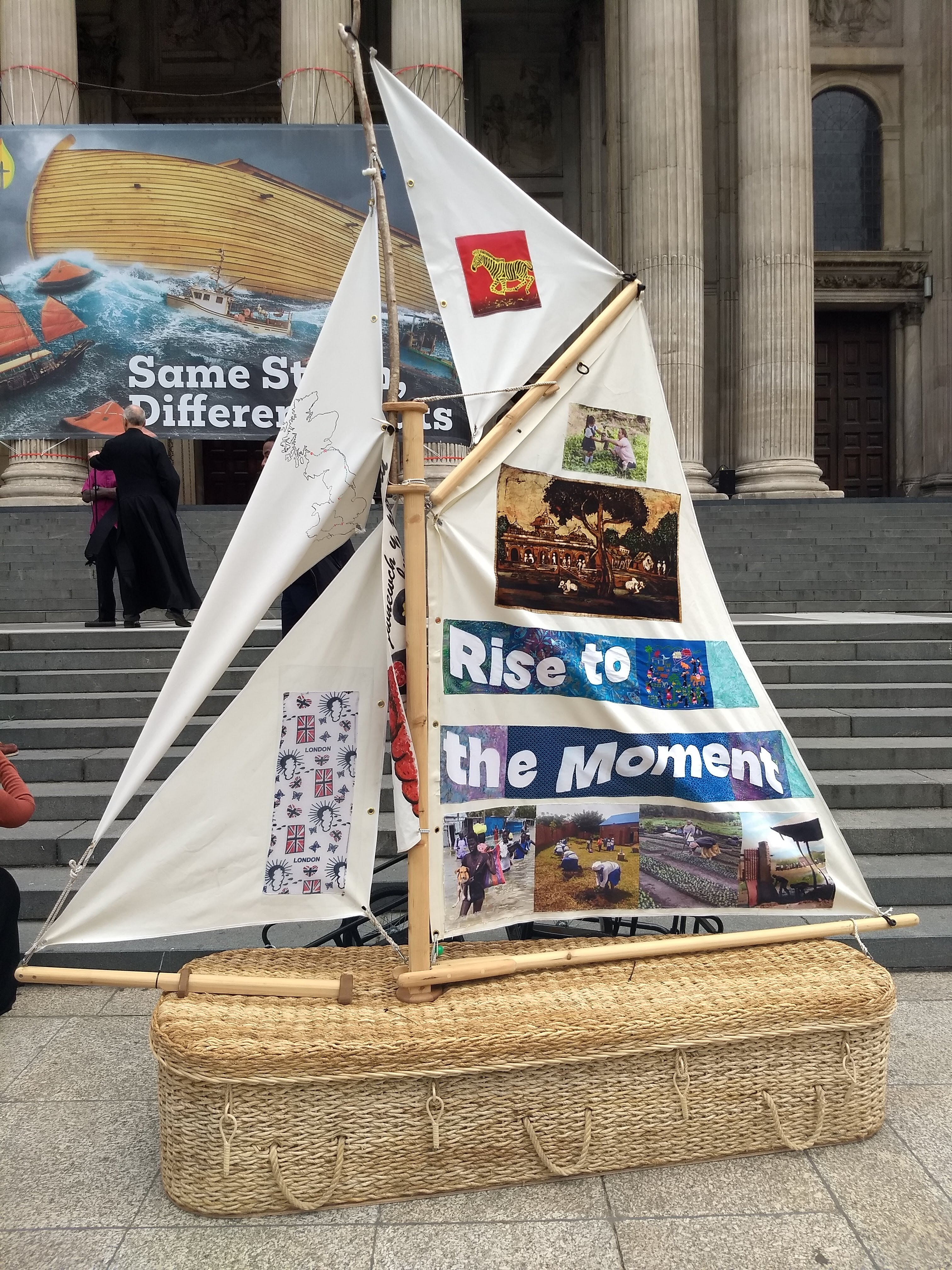 The pilgrim boat made of wicker, wood and banners with Rise to the Moment caption