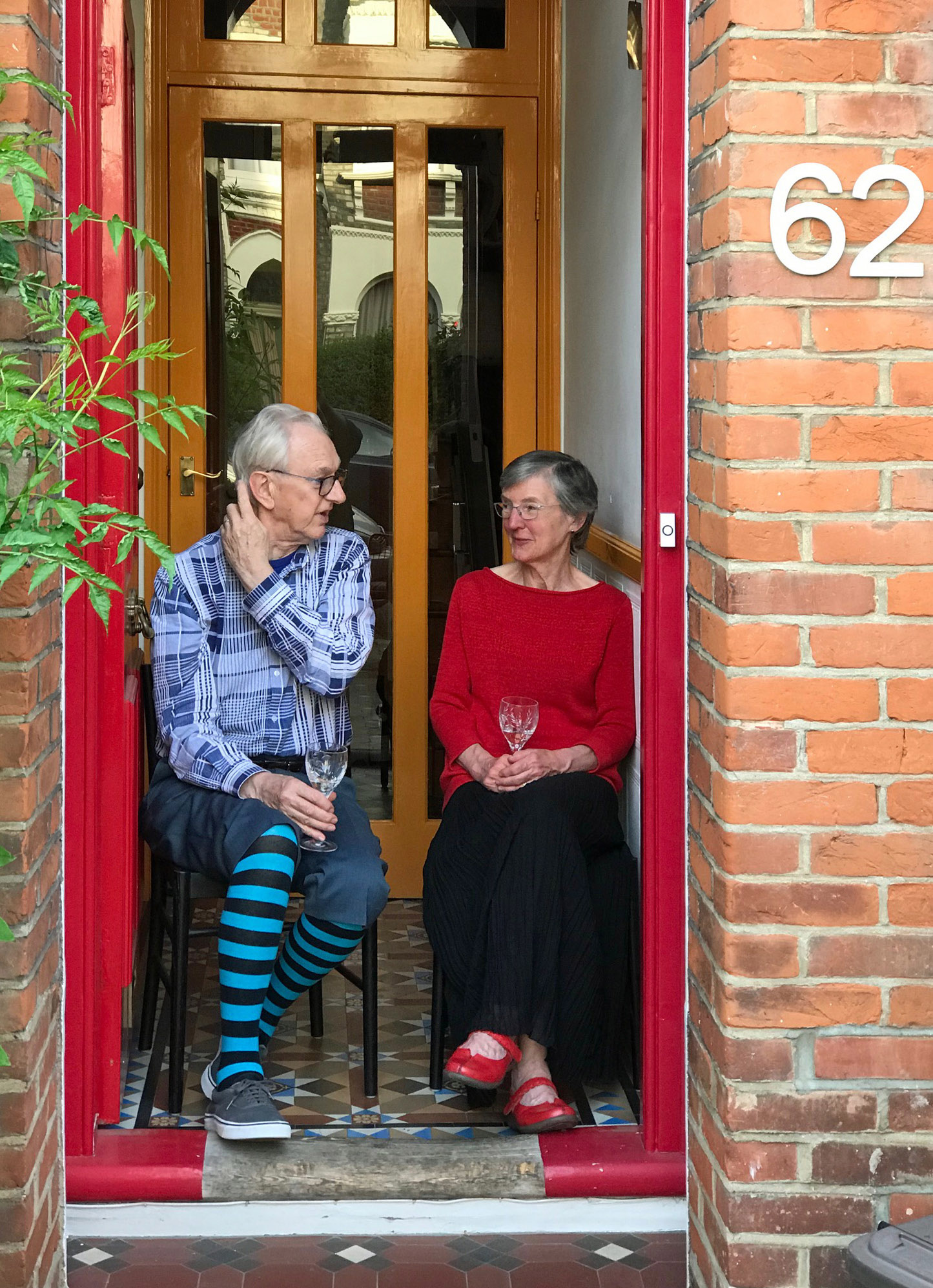 Image of Peter & Anne sitting in front of their front door with a class of wine in hand meeting friends during the first pandemic lockdown