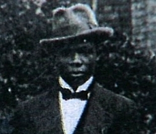 Black and white image of Frank Bates in a bow tie and bowler hat