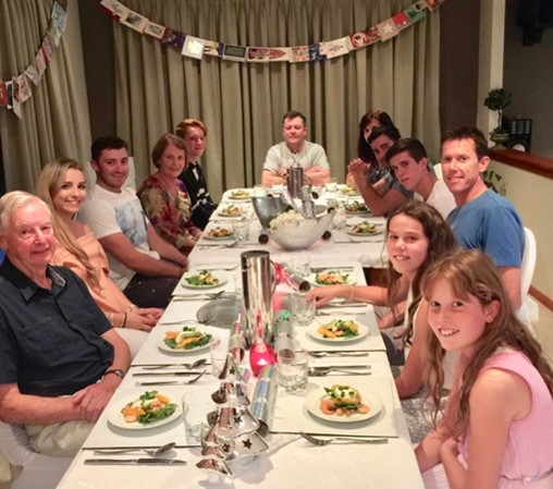 Large family sitting down to Christmas dinner in Australia