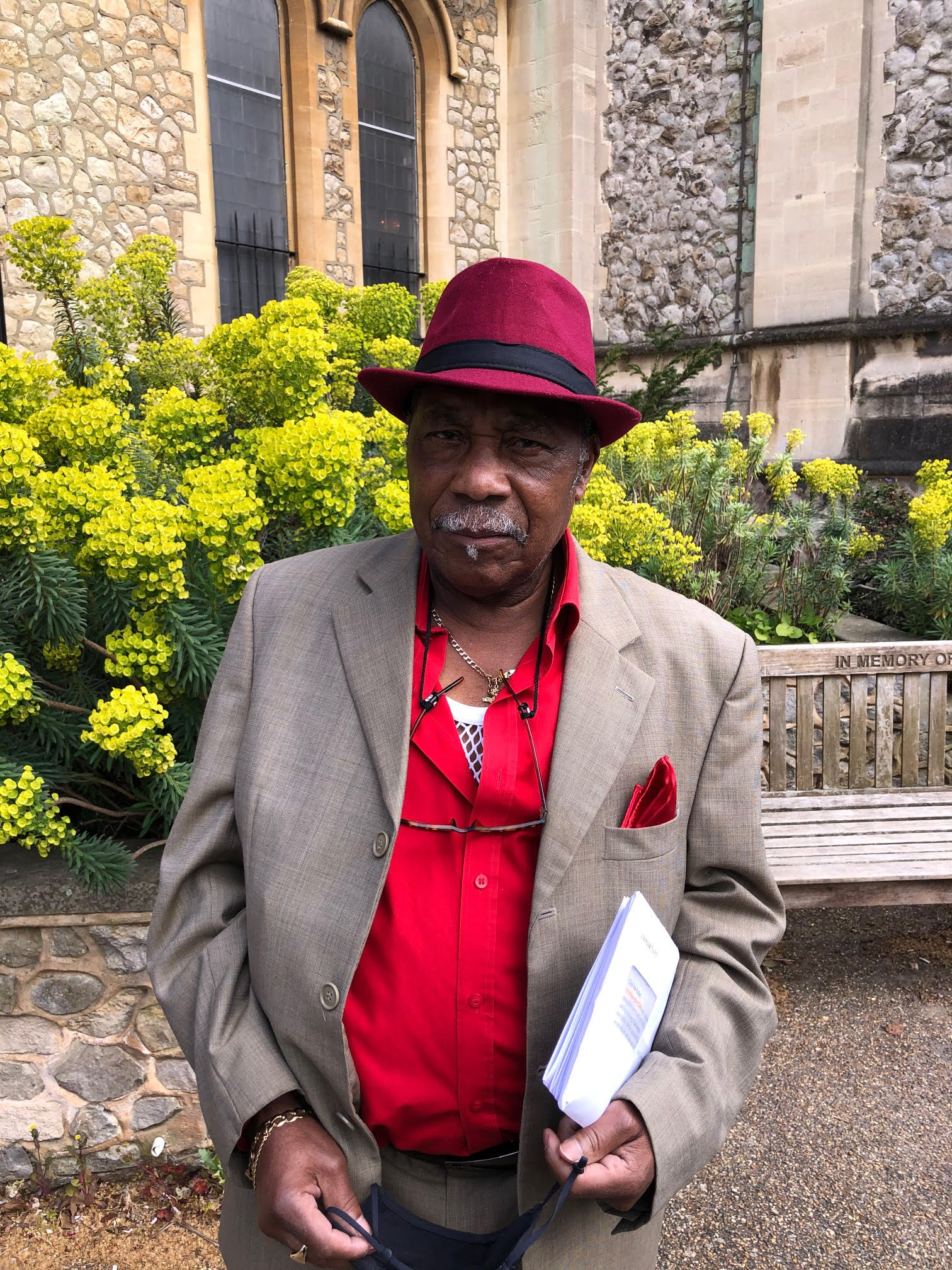 Image of Keith Watson. Wearing a beige suit, red shirt and maroon hat