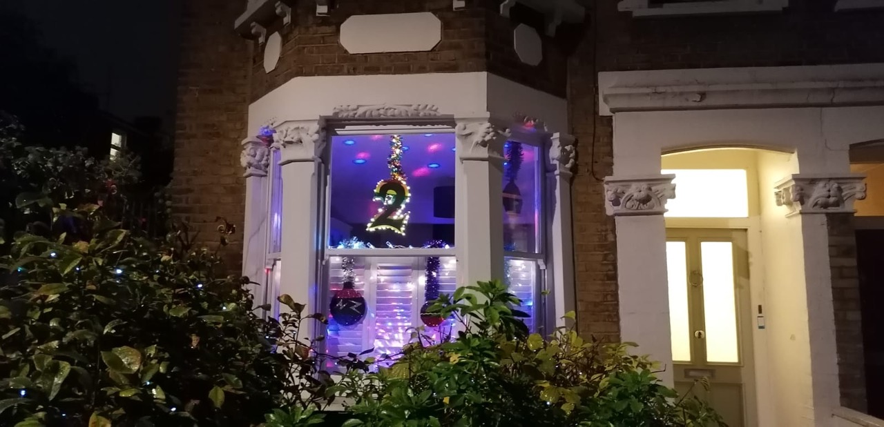 Window lit up with Christmas decorations and the number 2
