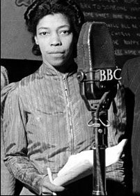 Black & white image of Una Marson standing in front of a BBC microphone