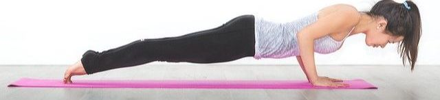 Woman on a pink yoga mat doing a push up