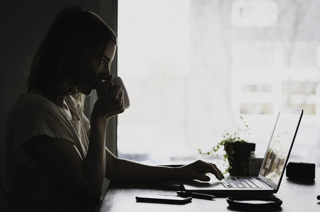 Woman drinking a cup of tea/coffee in front of a laptop.