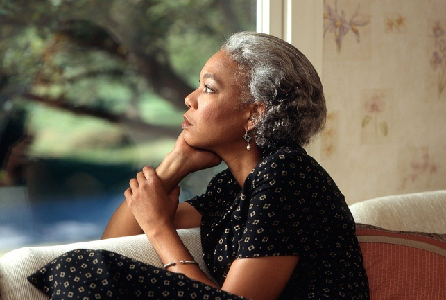 Woman staring out the window with a pensive look.