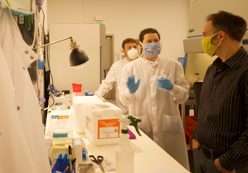 Two students, wearing masks, gloves and lab coats, stand at a lab bench and chat with a supervisor.