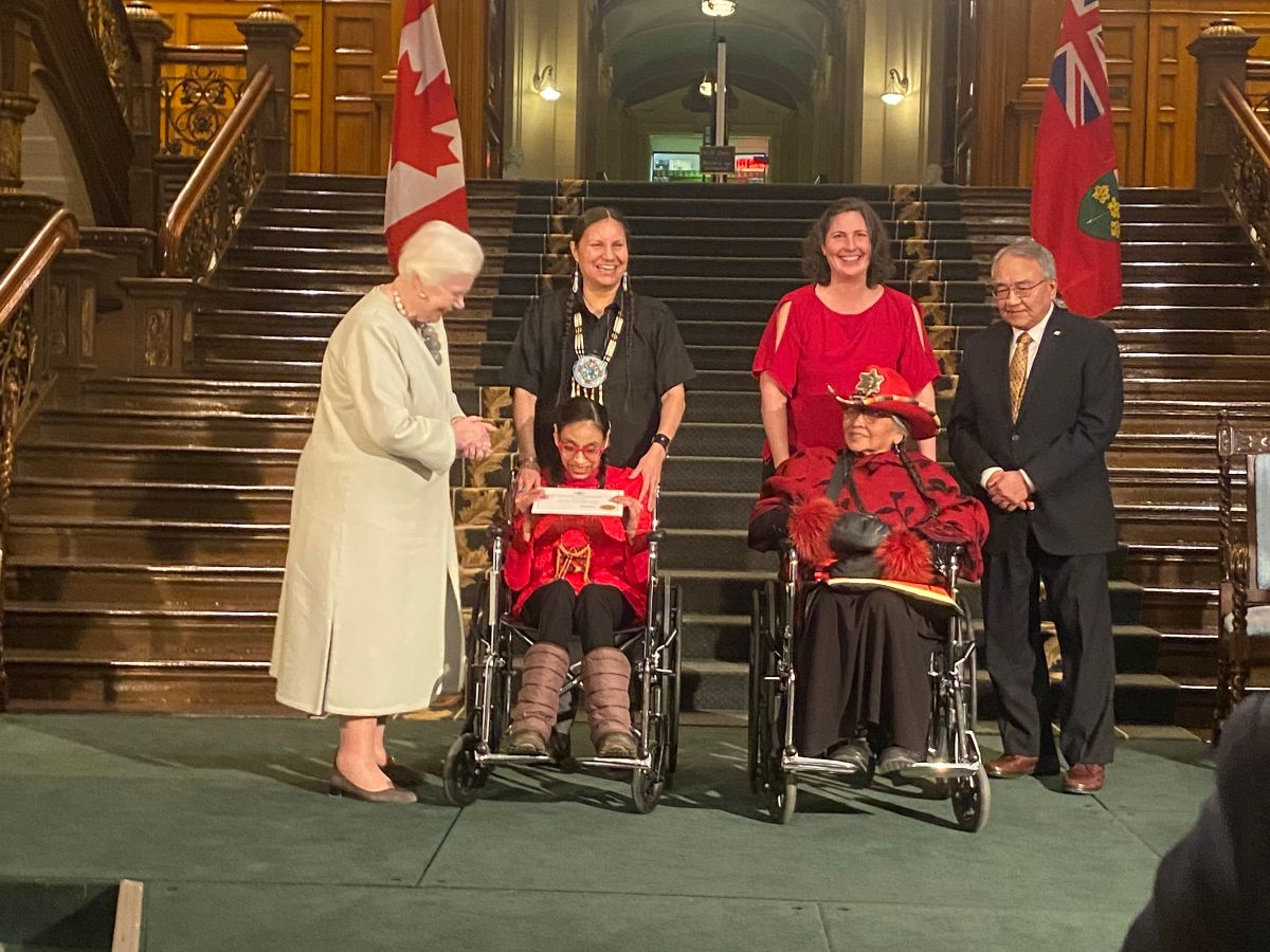 A photo of Dolleen Tisawii'ashii Manning, Sky Stonefish, Evadne Kelly, and Mona Stonefish on stage receiving the award from Elizabeth Dowdeswell.