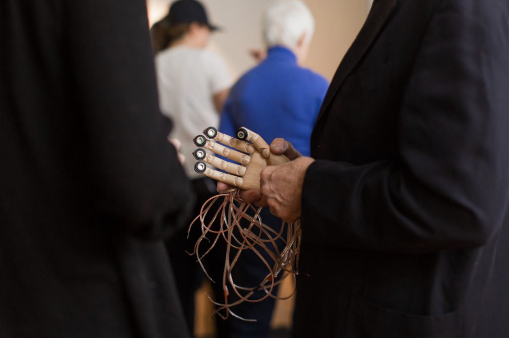 Photo from Cripping the Arts. A person's torso is visible in profile, holding a vibratactile hand with sensors on the fingertips, and a mess of wires coming out of it.
