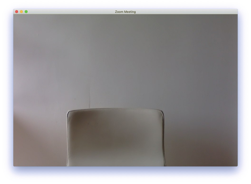 An empty, white chair sits in the center of a Zoom meeting window. There is a white background behind the chair with soft shadows.