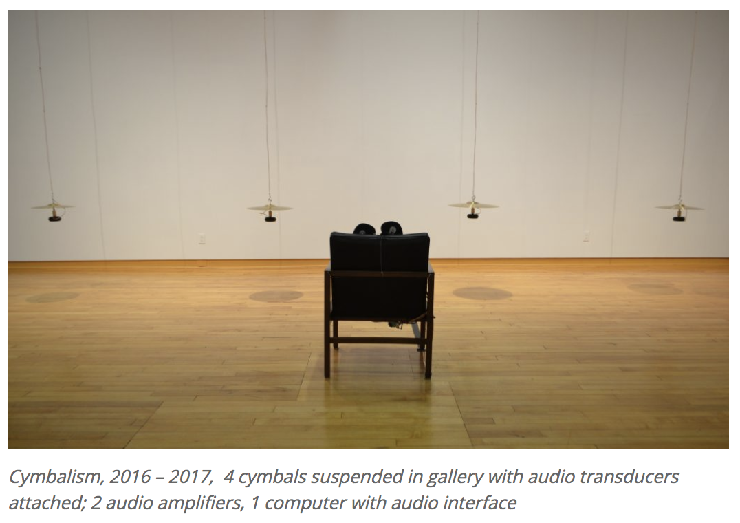 "Photo from ""Cymbalism."" A wheelchair in a gallery space sits in front of 4 suspended cymbals."