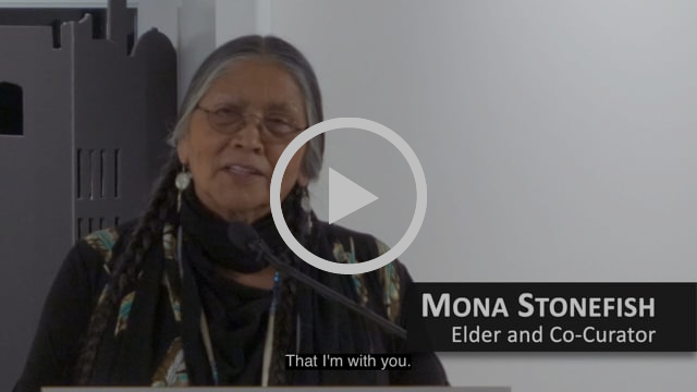 "Mona Stonefish speaks into a microphone. Mona is an Onkwehón:we Elder with long silver and black braids. Her name and title, ""Mona Stonefish Elder and Co-Curator,"" is displayed in the lower right corner of the video still. At the lower centre of the image there's a caption that reads, ""That I am with you."""