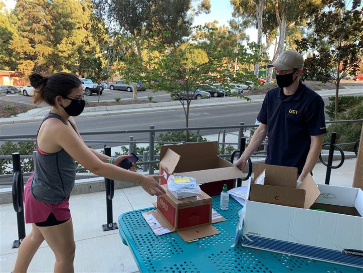 Graduate student Katherine Lawson picks up some ethernet supplies from Graduate Division's Turner Dahl, boxes and supplies piled on a blue table, with Turner and the student each wearing a face covering