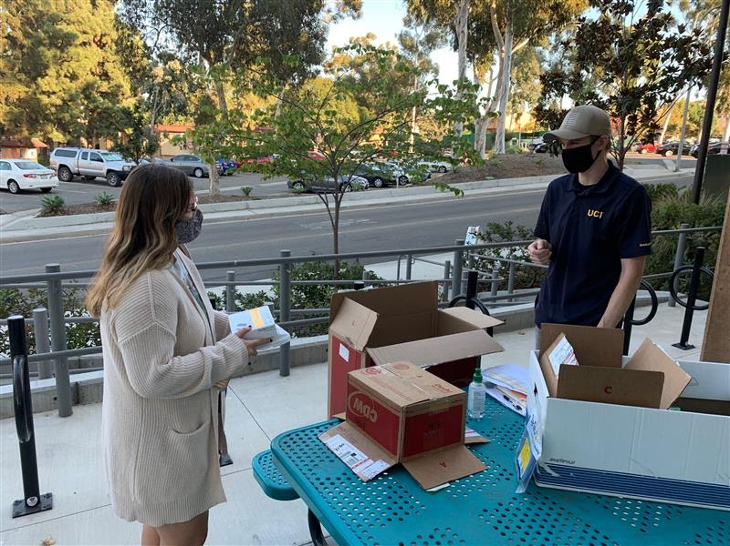 Graduate student Megan Cole picks up some ethernet supplies from Graduate Division's Turner Dahl, boxes and supplies piled on a blue table, with Turner and the student each wearing a face covering