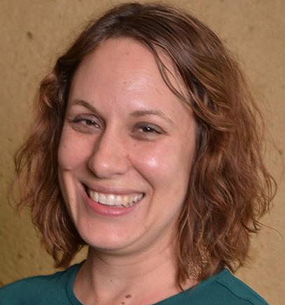 Image of Rebecca Dingo smiling, wearing blue shirt with tan background