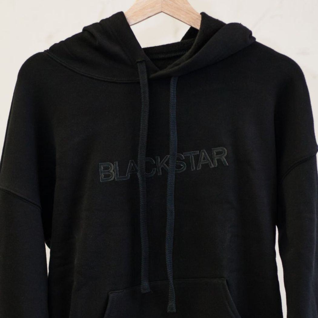 "A photo of a BlackStar hooded sweatshirt on a hanger (against a tan wall) in all black, with black lettering across the chest that reads ""BlackStar."""