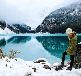 Woman Hiking in Snow Next to Turquoise Mountain Lake