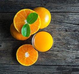 Oranges and Orange Juice on Dark Gray Wood Table