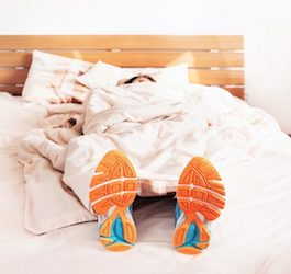 Person Sleeping on Bed while Wearing Running Shoes