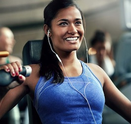 Woman in Blue Sport-Top with White Earbuds Working out on Weight Machine