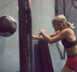 Woman Throwing Medicine Ball at Wall of Gym