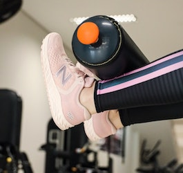 Woman's Legs with Pink Shoes on Weightlifting Machine